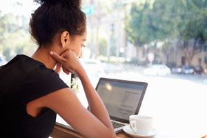 A woman using VPN on her laptop in a coffee shop