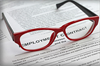 Employment contract with woman's red glasses on top of it