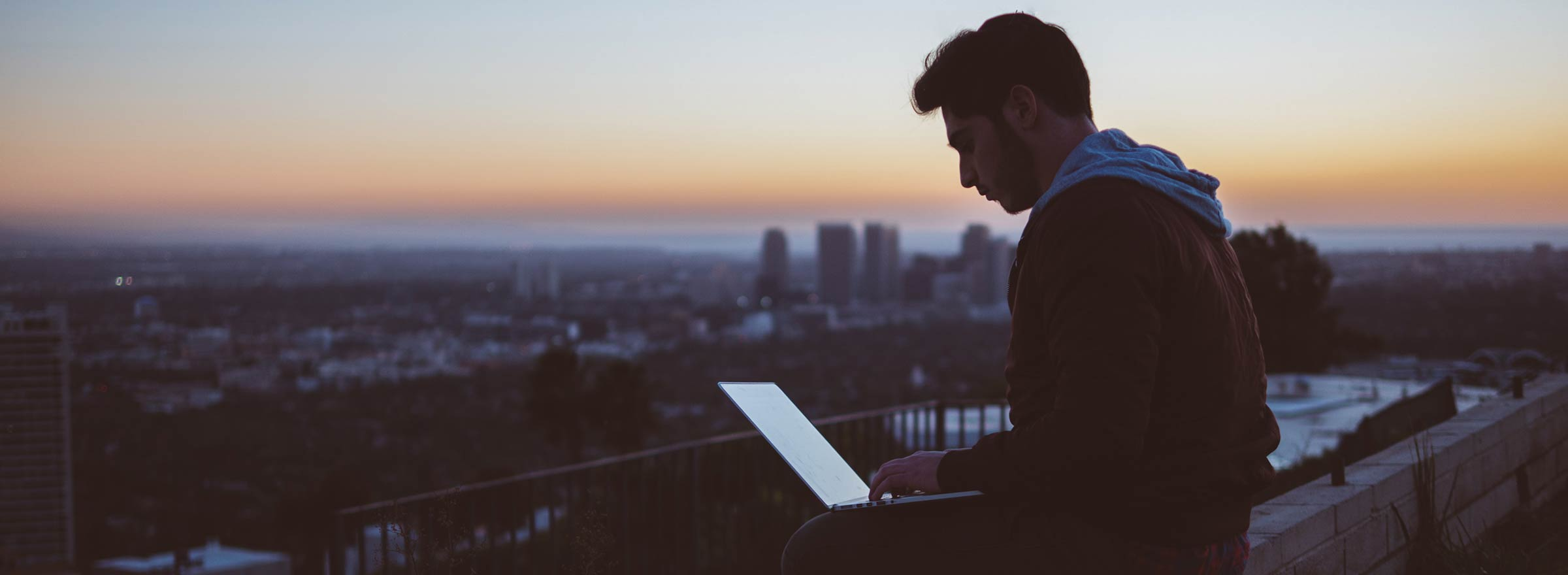A young man sitting on a rooftop at sunset, typing on his laptop, representing data privacy concerns for nonprofits