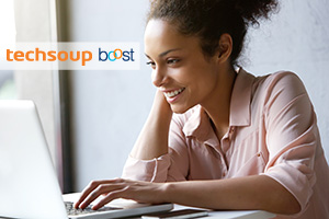 Woman at laptop with TechSoup Boost logo