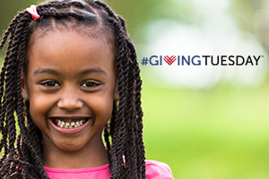 Girl smiling with Giving Tuesday logo