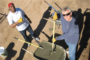 Two Arizona Baptist Children's Services volunteers mixing concrete